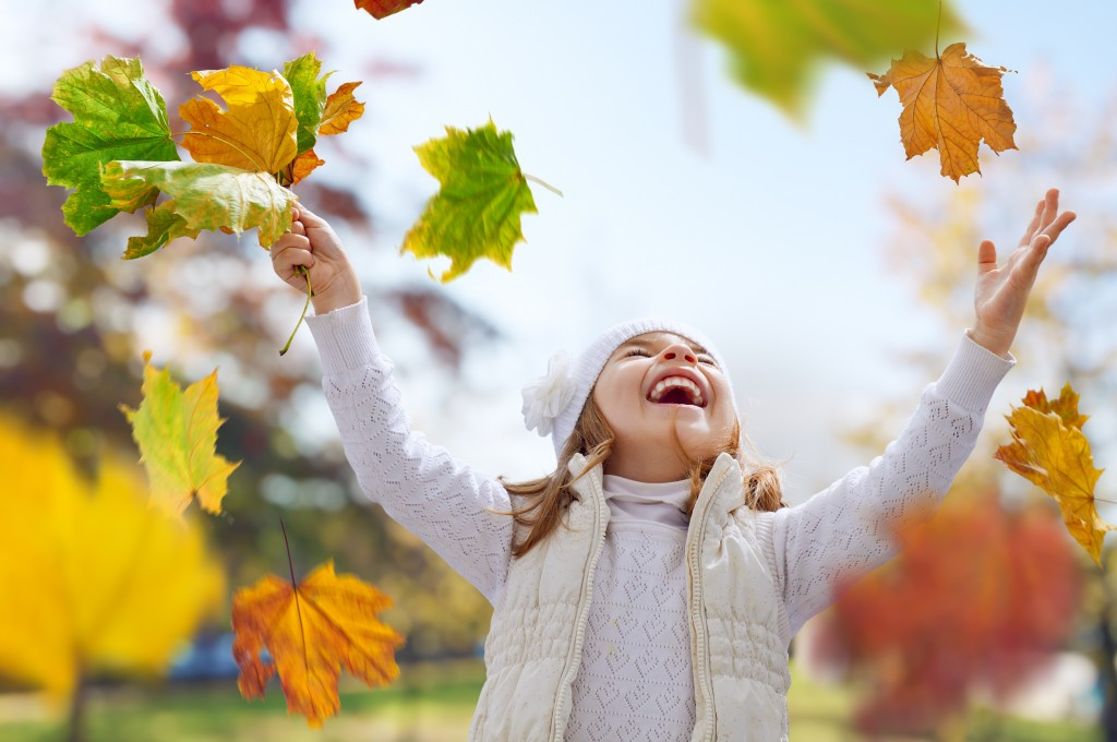 Girl catching falling leaves